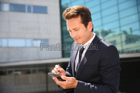 businessman sitting outside and checking on