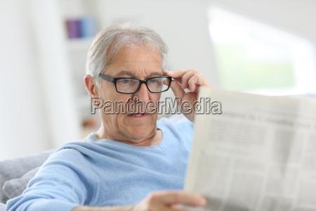 senior mann zu hause lesen zeitung