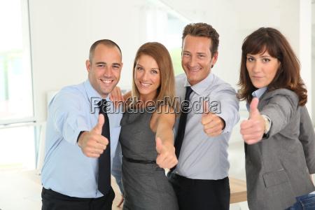 erfolgreiches geschaeftsteam das sich daumen zeigt