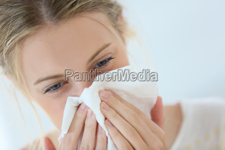 young woman with cold blowing her