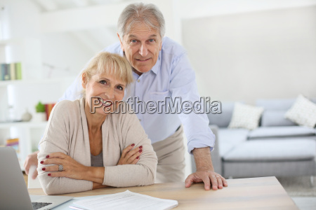 senior couple at home filling pension