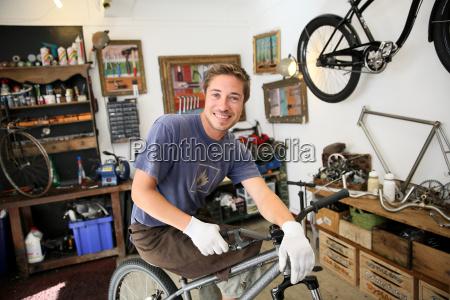 portraet von smilng handwerker in fahrradwerkstatt