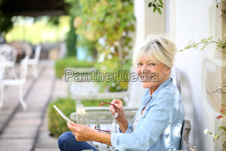 senior woman relaxing outside and using