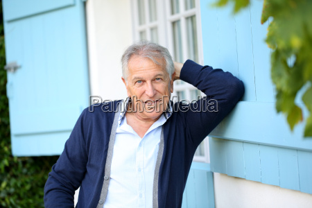 senior man leaning on wall outside