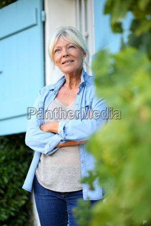 senior woman standing outside the house