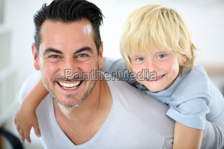 portrait of father carrying son on