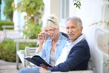senior paar lesebuch vor ihrem haus
