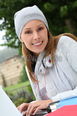 young woman in park studying on