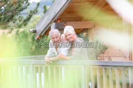 senior couple standing oustide log cabin