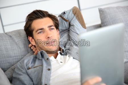 attractive man at home using digital