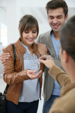 happy young couple getting key of