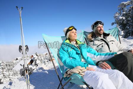 couple of skiers sunbathing in long