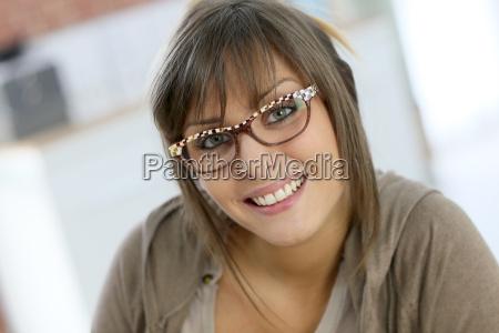 laechelnde junge frau traegt brille