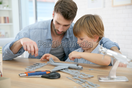 father and son assembling airplane mock
