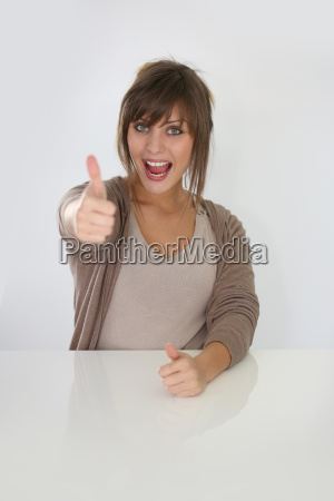 portrait of cheerful woman showing thumbs