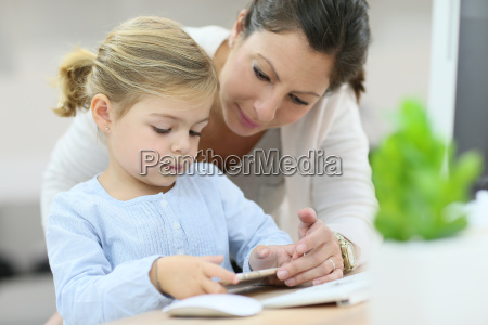 mother and daughter using smartphone home