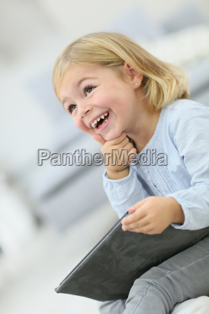 little blond girl using tablet with