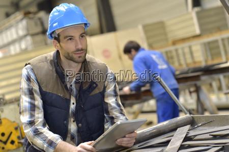 engineer in metallurgical factory using tablet