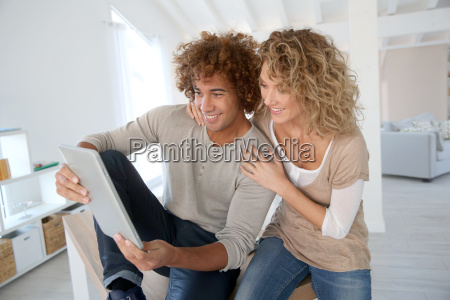 happy couple at home websurfing on