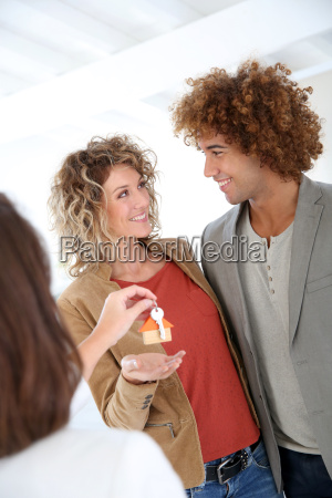 cheerful couple getting keys of their