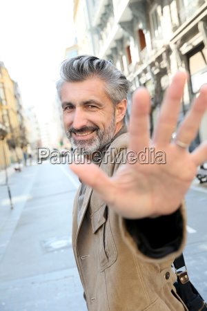 handsome middle aged man showing hand