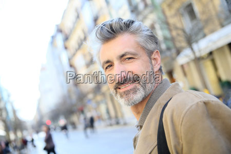 handsome mature man walking in town