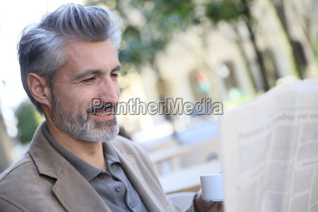 mature man in town reading newspaper