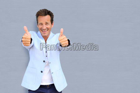 cheerful mature man showing thumbs up