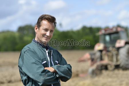 portraet laechelnder landwirt auf bewirtschafteten flaechen