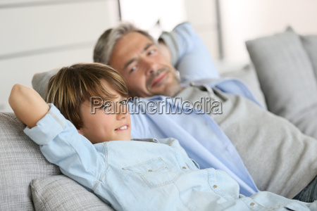 father and son relaxing in sofa