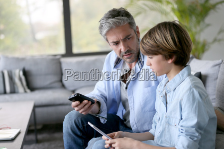 father and son playing with smartphones