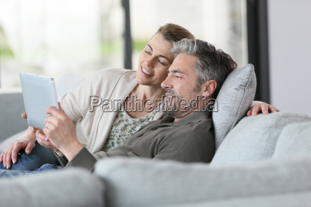 mature couple using digital tablet relaxing