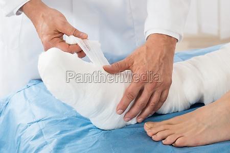 doktor binden bandage auf patienten bein