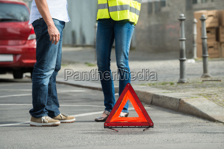 couple standing near triangular warning sign