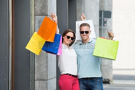 paar holding mehrfarbige einkaufstasche