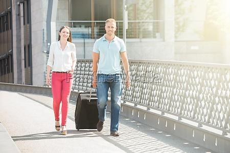 young couple walking on bridge with