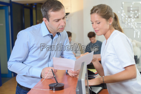 man showing paperwork to lady at