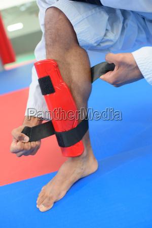 martial artist attaching leg guard