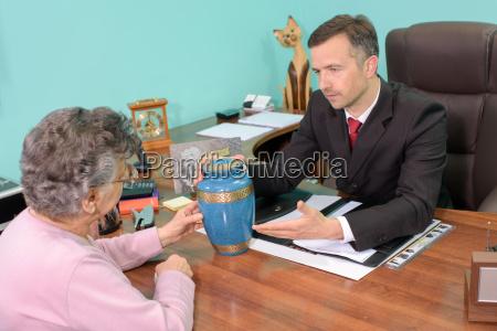 dyrektor pogrzebowy z kobieta patrzac na