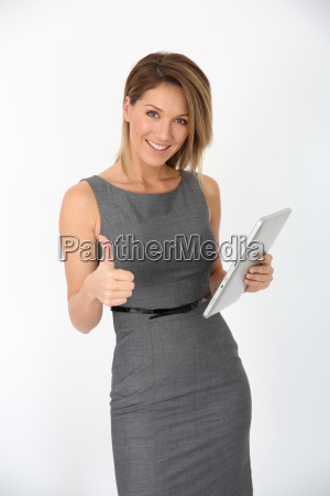 cheerful businesswoman with pad showing thumb