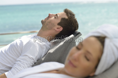 couple relaxing in long chairs outside