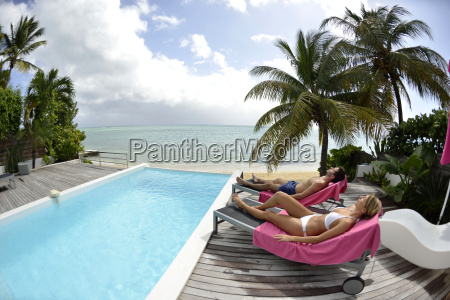 couple relaxing in long chair by