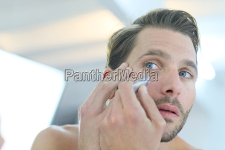 man in front of mirror using