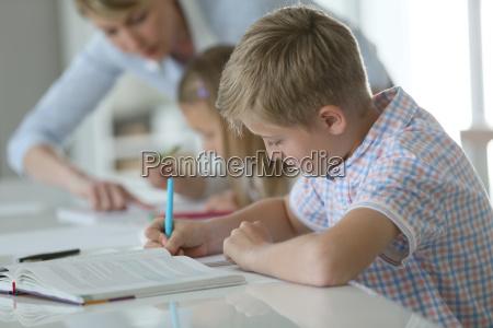 schueler im klassenzimmer schriftlich auf notebook