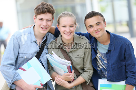 portrait of cheerful students holding books