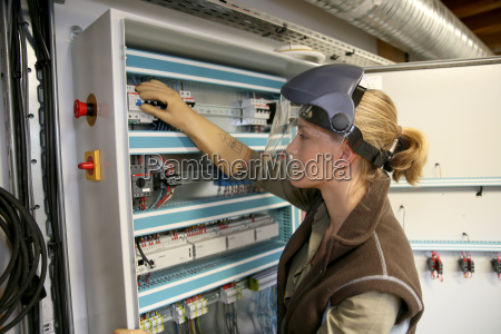young woman checking electrical system of