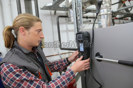 techniker ueberprueft waermepumpenintensitaet mit elektronischem geraet