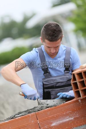 junge ziegelsteinschicht die draussen an backsteinmaueraufbau