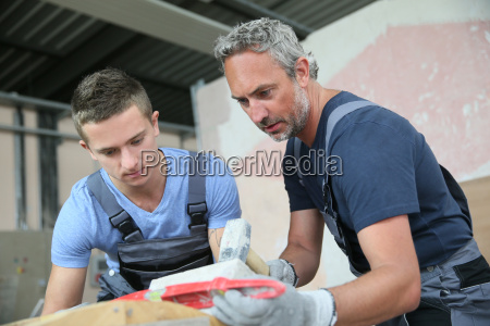teenager with professional brick layer in