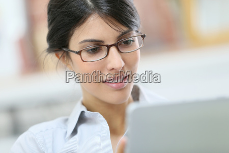 young woman with eyeglasses using digital